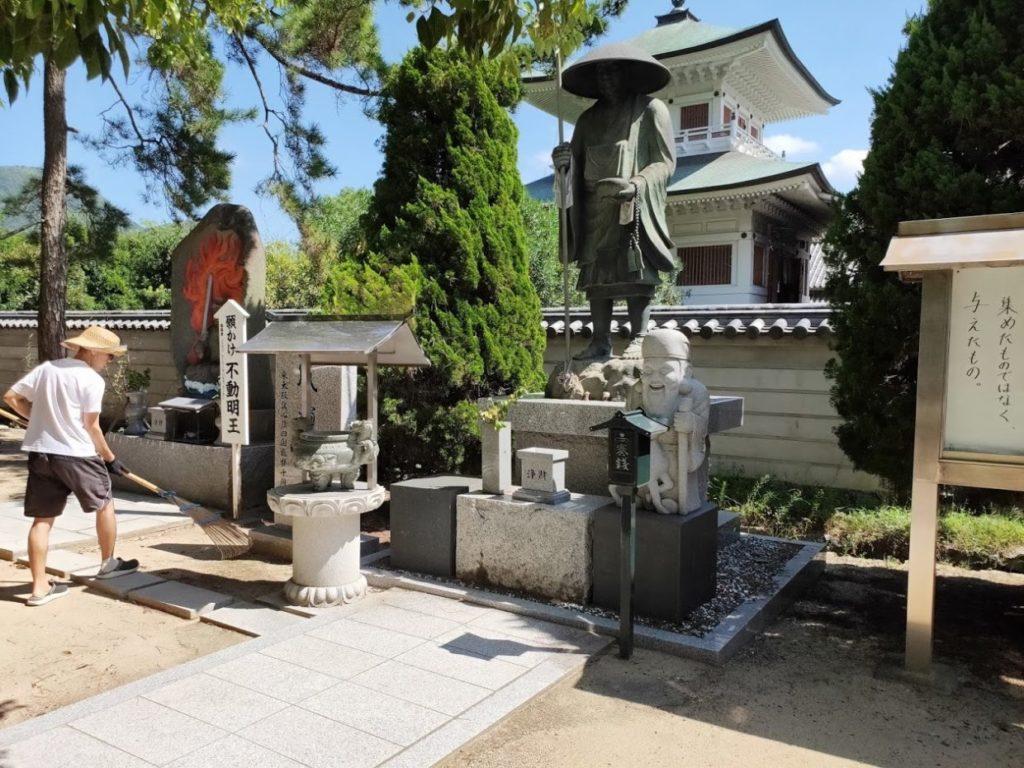 80番国分寺の仏像と掃除をする住職