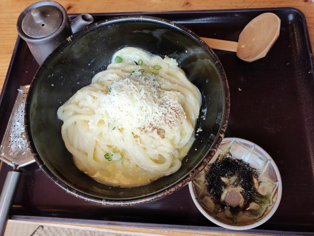蒜山手打ちうどんやす坊の高原の釜玉うどんのチーズを削る