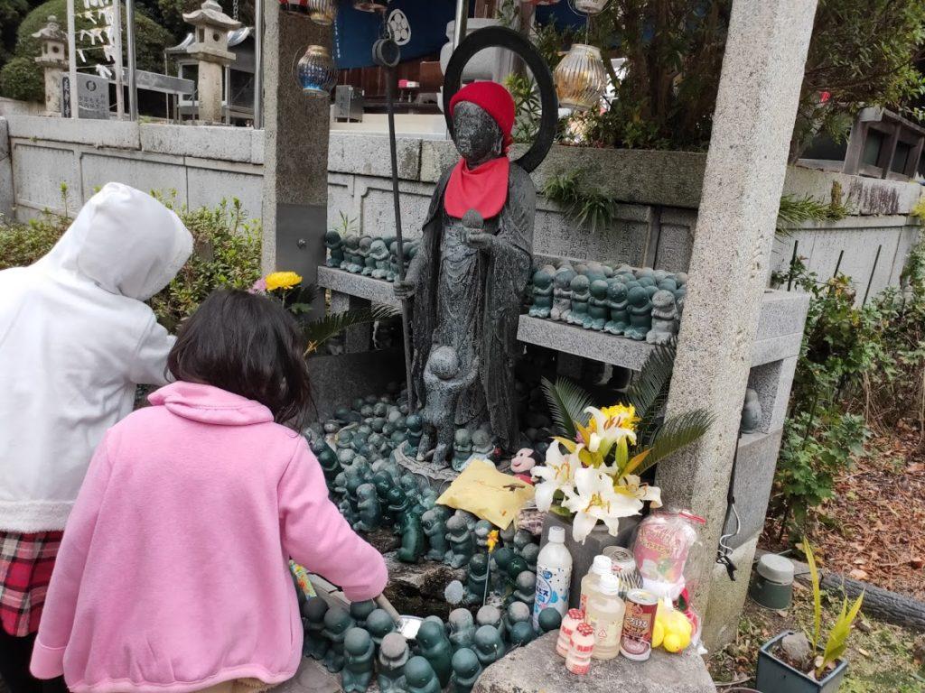 54番延命寺で水子地蔵に水をかける子ども