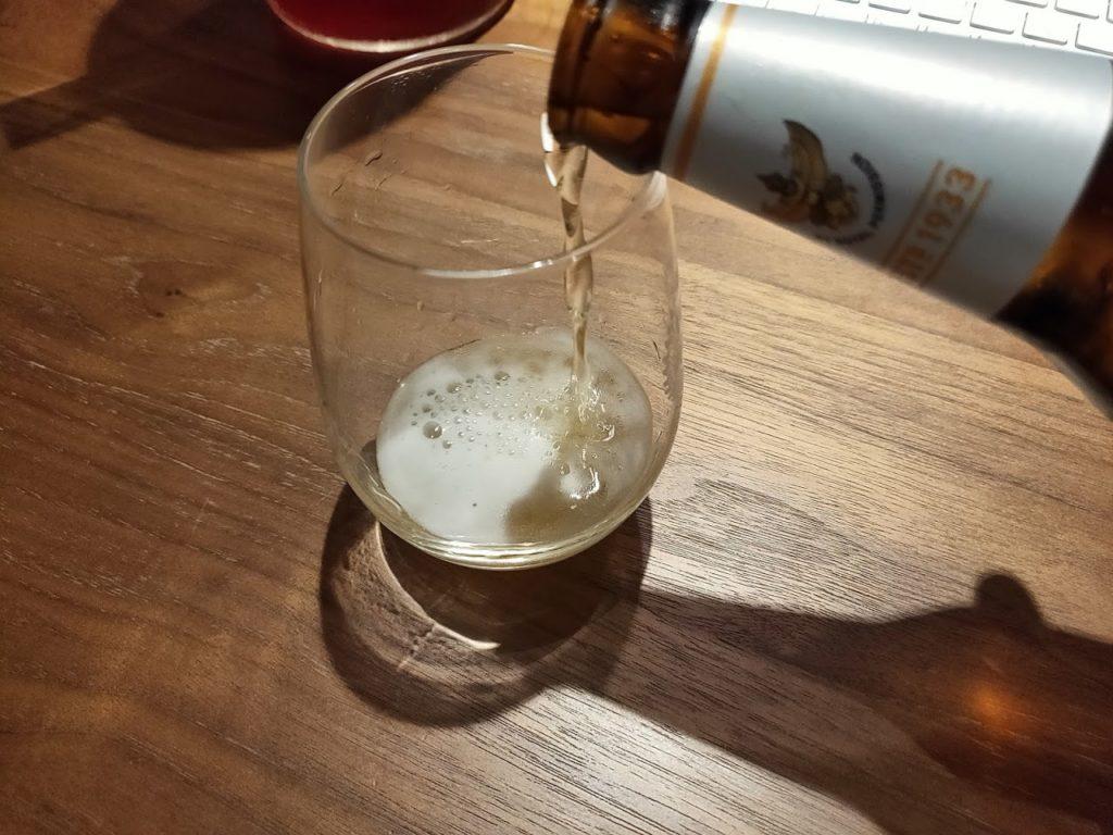 シンハービールをグラスに注ぐ