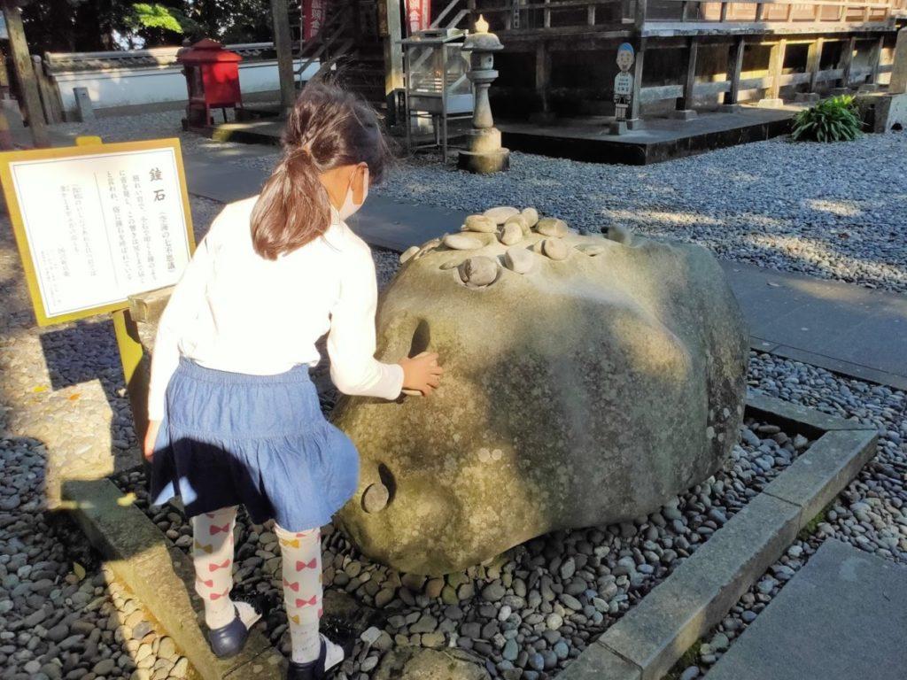 24番最御崎寺の鐘石を鳴らす子ども